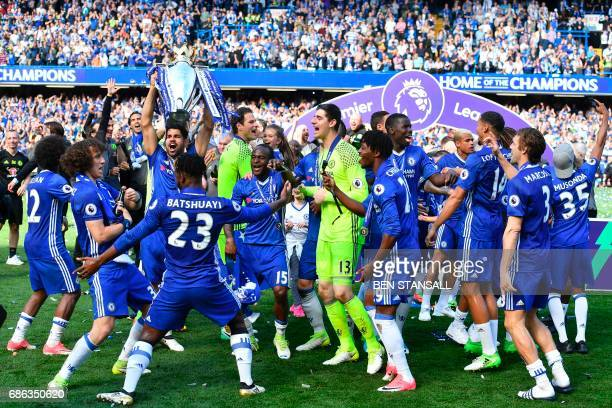 Chelsea's Brazilianborn Spanish striker Diego Costa holds up the English Premier League trophy as players celebrate their league title win at the end...