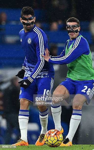 Chelsea's Brazilianborn Spanish striker Diego Costa wears a face mask as he warms up with Chelsea's Spanish defender Cesar Azpilicueta ahead of the...