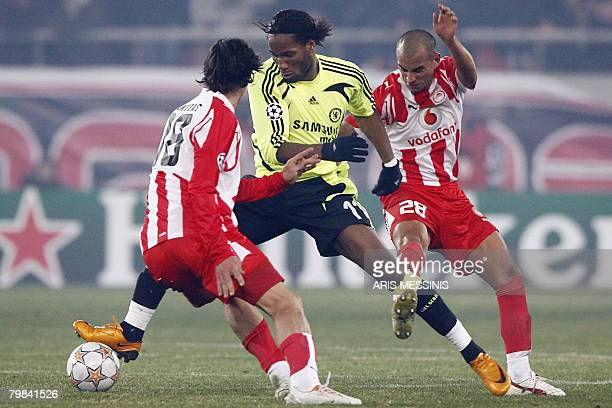 Chelsea's Didier Drogba challenges for the ball with Olympiakos' Cristian Ledesma during their first knock out round Champions League football game...