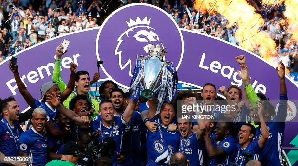 Chelsea's English defender Gary Cahill and Chelsea's English defender John Terry hold up the Premier League trophy as players celebrate their league...