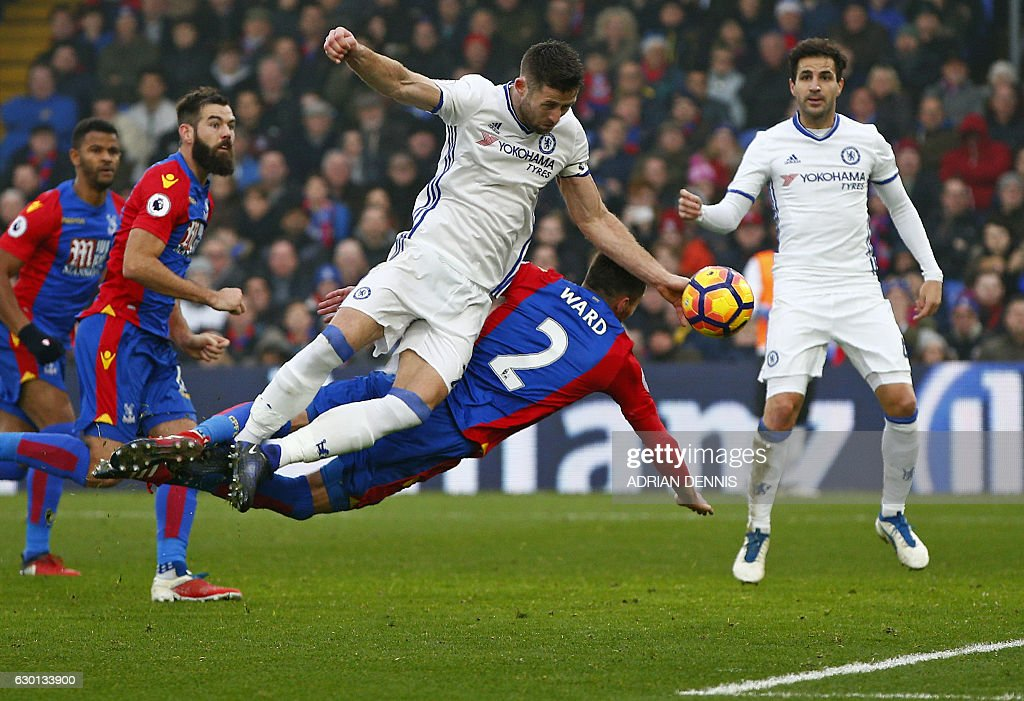 Chelsea's English defender Gary Cahill (L) dives tohead the ball towards goal, after it rebounded off of the post following Chelsea's Spanish defender Marcos Alonso's free-kick, during the English Premier League football match between Crystal Palace and Chelsea at Selhurst Park in south London on December 17, 2016. / AFP / Adrian DENNIS / RESTRICTED TO EDITORIAL USE. No use with unauthorized audio, video, data, fixture lists, club/league logos or 'live' services. Online in-match use limited to 75 images, no video emulation. No use in betting, games or single club/league/player publications. /