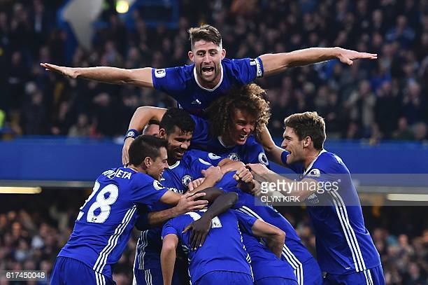 TOPSHOT Chelsea's English defender Gary Cahill jumps onto the huddle to join the celebrates after Chelsea's French midfielder N'Golo Kante scored...