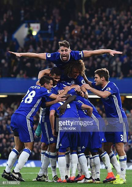 Chelsea's English defender Gary Cahill jumps onto the huddle to join the celebrates after Chelsea's French midfielder N'Golo Kante scored their...