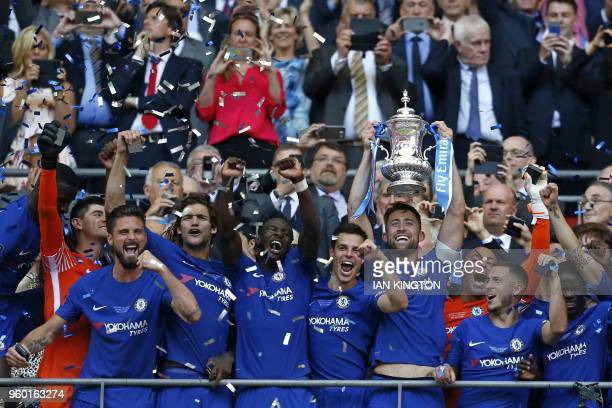 Chelsea's English defender Gary Cahill lifts the trophy as Chelsea players celebrate their win after the English FA Cup final football match between...