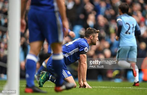 Chelsea's English defender Gary Cahill reacts after scoring an owngoal during the English Premier League football match between Manchester City and...