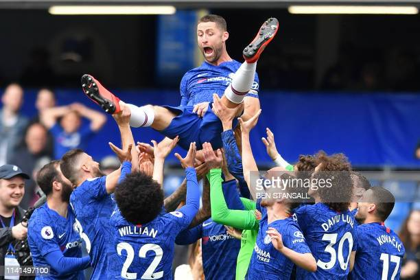 TOPSHOT Chelsea's English defender Gary Cahill reacts as teammates throw him in the air following the English Premier League football match between...