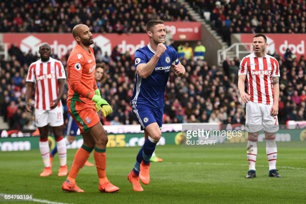 Chelsea's English defender Gary Cahill runs to celebrate past Stoke City's English goalkeeper Lee Grant after Chelsea's Brazilian midfielder Willian...