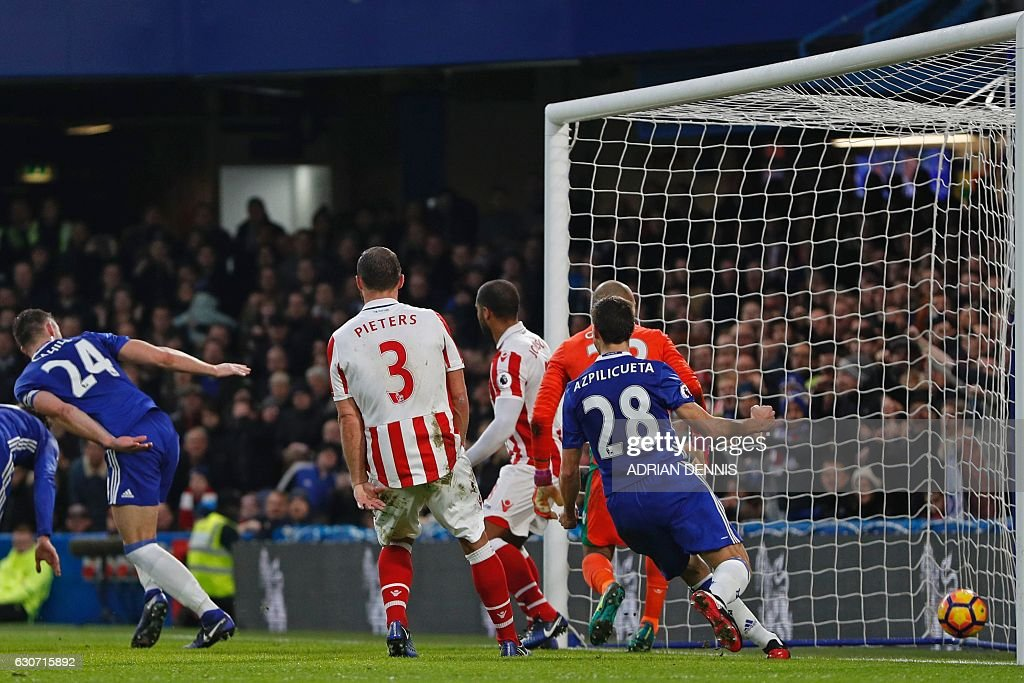 Chelsea's English defender Gary Cahill (L) scores the opening goal of the English Premier League football match between Chelsea and Stoke City at Stamford Bridge in London on December 31, 2016. / AFP / Adrian DENNIS / RESTRICTED TO EDITORIAL USE. No use with unauthorized audio, video, data, fixture lists, club/league logos or 'live' services. Online in-match use limited to 75 images, no video emulation. No use in betting, games or single club/league/player publications. /
