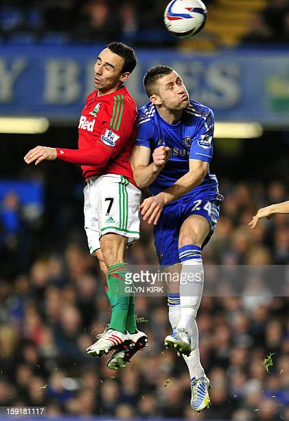 Chelsea's English defender Gary Cahill vies with Swansea City's English midfielder Leon Britton during the English League Cup first leg semifinal...