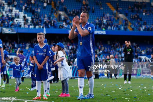 Chelsea's English defender John Terry applauds as players celebrate their league title win on the pitch at the end of the Premier League football...