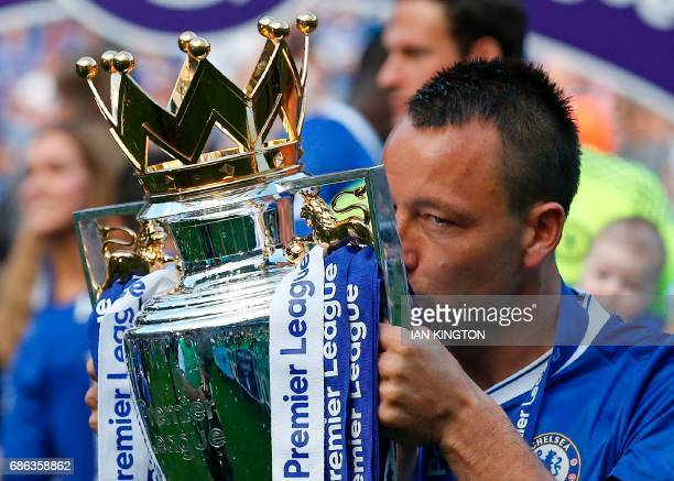 Chelsea's English defender John Terry kisses the English Premier League trophy as players celebrate their league title win at the end of the Premier...