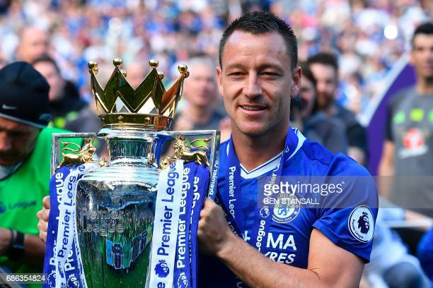 Chelsea's English defender John Terry poses with the English Premier League trophy as players celebrate their league title win at the end of the...
