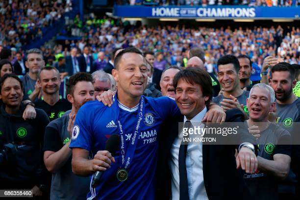 Chelsea's English defender John Terry stands with Chelsea's Italian head coach Antonio Conte, as players celebrate their league title win at the end...