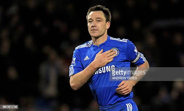 Chelsea's English defender John Terry touches his Chelsea badge as he leaves the pitch after the final whistle in the English Premier League football...
