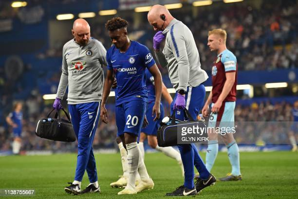 TOPSHOT Chelsea's English midfielder Callum HudsonOdoi receives medical attention after picking up an injury during the English Premier League...