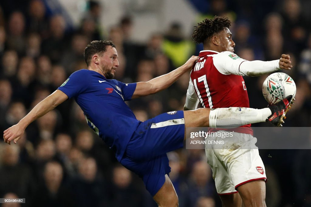 TOPSHOT - Chelsea's English midfielder Danny Drinkwater (L) vies with Arsenal's Nigerian striker Alex Iwobi during the English League Cup semi-final first leg football match between Chelsea and Arsenal at Stamford Bridge in London on January 10, 2018. / AFP PHOTO / Adrian DENNIS / RESTRICTED TO EDITORIAL USE. No use with unauthorized audio, video, data, fixture lists, club/league logos or 'live' services. Online in-match use limited to 75 images, no video emulation. No use in betting, games or single club/league/player publications. /