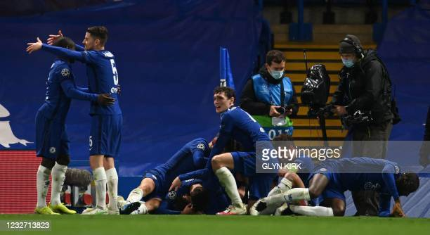 Chelsea's English midfielder Mason Mount is mobbed by teammates after scoring the second goal during the UEFA Champions League second leg semi-final...