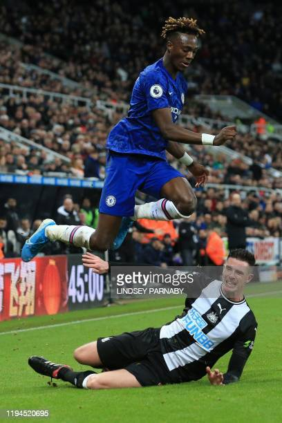 Chelsea's English striker Tammy Abraham jumps a tackle from Newcastle United's Irish defender Ciaran Clark during the English Premier League football...