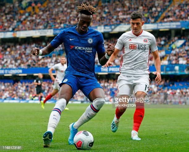 Chelsea's English striker Tammy Abraham shields the ball from Sheffield United's Irish defender John Egan during the English Premier League football...
