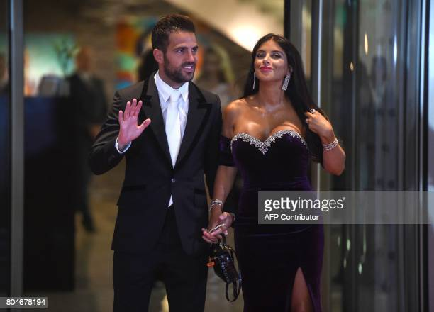 Chelsea's football player Cesc Fabregas and his wife pose on a red carpet upon arrival to attend Argentine football star Lionel Messi and Antonella...