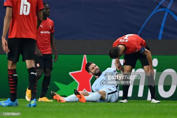 Chelsea's French forward Olivier Giroud is helped by Rennes' French defender Damien Da Silva during the UEFA Champions League Group E football match...