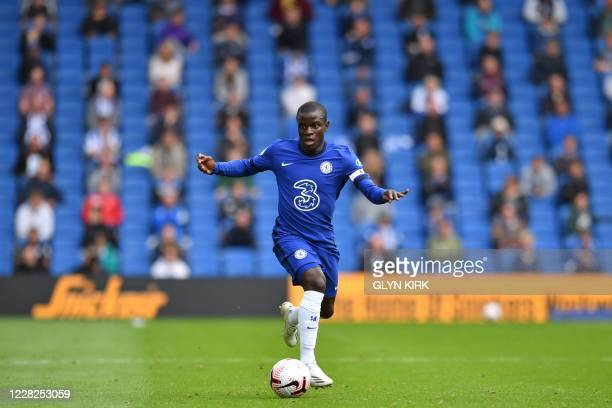 Chelsea's French midfielder N'Golo Kante runs with the ball as socially distanced fans watch from the stands during the preseason friendly football...