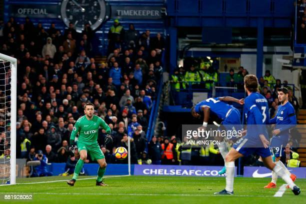 Chelsea's German defender Antonio Rudiger heads the opening goal past Swansea City's Polish goalkeeper Lukasz Fabianski during the English Premier...