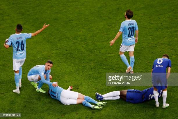 Chelsea's German defender Antonio Ruediger and Manchester City's Belgian midfielder Kevin De Bruyne react in pain after a collision during the UEFA...