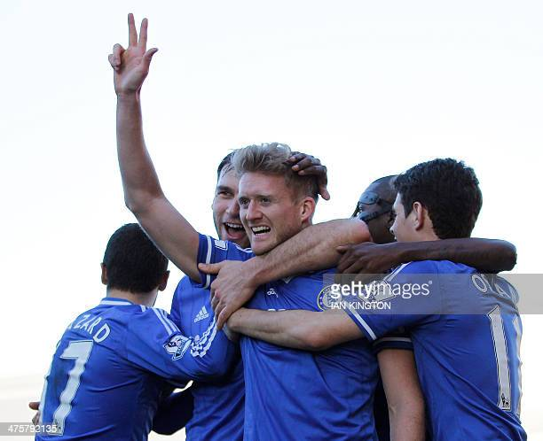 Chelsea's German striker Andre Schurrle is mobbed by teammates as he celebrates scoring his third goal to complete his hattrick during the English...