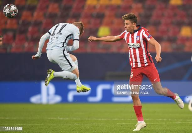 Chelsea's German striker Timo Werner jumps for the ball next to Atletico Madrid's Spanish midfielder Marcos Llorente during the UEFA Champions League...