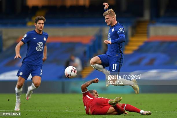 Chelsea's German striker Timo Werner jumps over a challenge from Liverpool's Spanish midfielder Thiago Alcantara during the English Premier League...