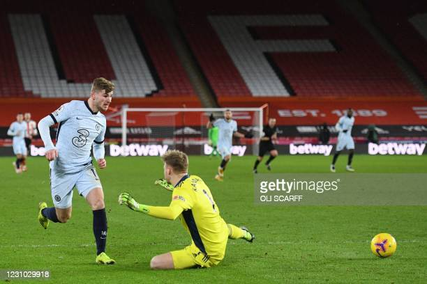 Chelsea's German striker Timo Werner passes the ball past Sheffield United's English goalkeeper Aaron Ramsdale before colliding with him resulting in...