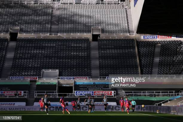 Chelsea's German striker Timo Werner runs with the ball in front of empty stands during the English Premier League football match between Newcastle...