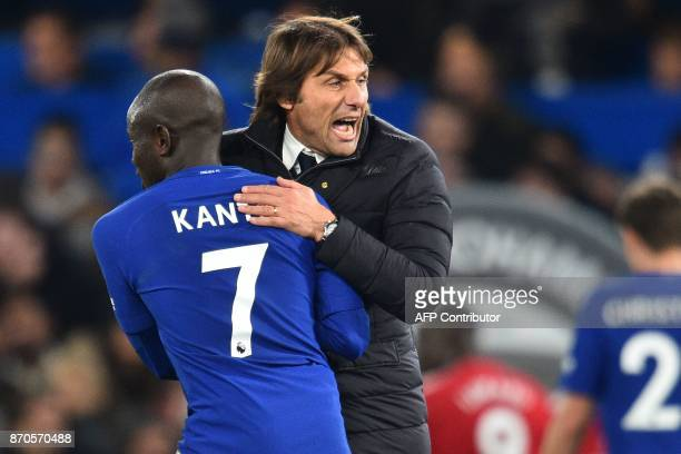 Chelsea's Italian head coach Antonio Conte celebrates on the pitch with Chelsea's French midfielder N'Golo Kante after the English Premier League...