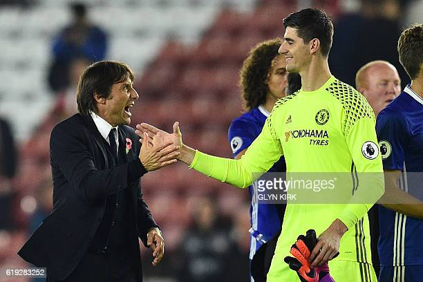 Chelsea's Italian head coach Antonio Conte celebrates with Chelsea's Belgian goalkeeper Thibaut Courtois on the pitch after the English Premier...