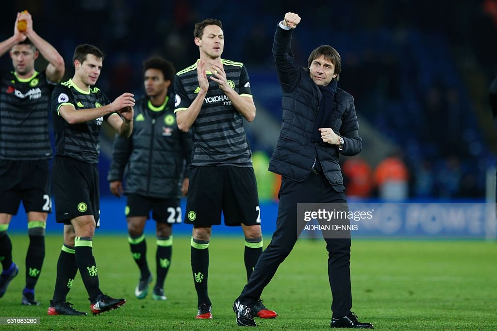 Chelsea's Italian head coach Antonio Conte (R) celebrates with his players on the pitch after the English Premier League football match between Leicester City and Chelsea at King Power Stadium in Leicester, central England on January 14, 2017. Cheslea won the game 3-0. / AFP / Adrian DENNIS / RESTRICTED TO EDITORIAL USE. No use with unauthorized audio, video, data, fixture lists, club/league logos or 'live' services. Online in-match use limited to 75 images, no video emulation. No use in betting, games or single club/league/player publications. /