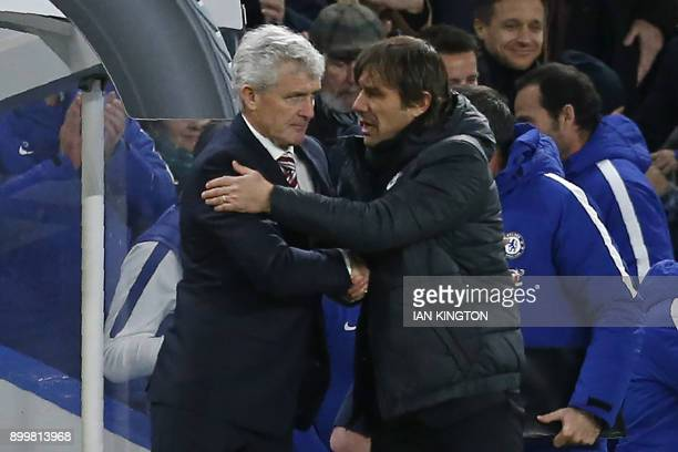 Chelsea's Italian head coach Antonio Conte consoles Stoke City's Welsh manager Mark Hughes after the English Premier League football match between...