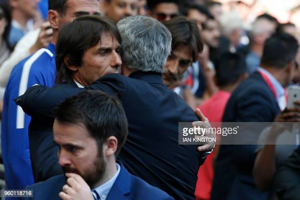Chelsea's Italian head coach Antonio Conte embraces Manchester United's Portuguese manager Jose Mourinho before the English FA Cup final football...