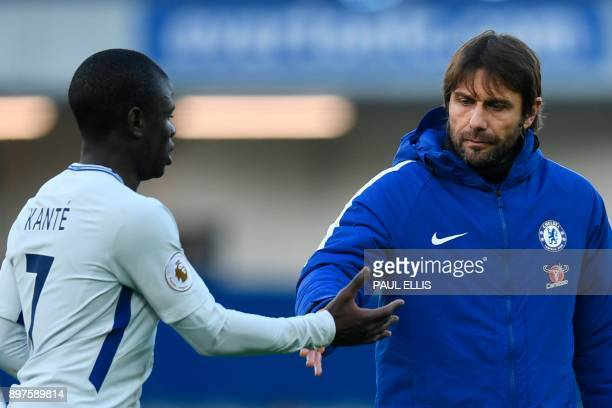 Chelsea's Italian head coach Antonio Conte gestures to Chelsea's French midfielder N'Golo Kante on the pitch after the English Premier League...