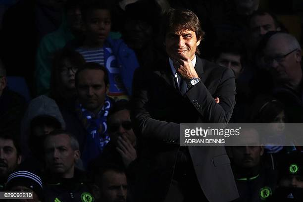 Chelsea's Italian head coach Antonio Conte watches from the touchline in the sunshine during the English Premier League football match between...