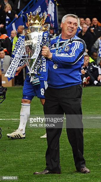 Chelsea's Italian manager Carlo Ancelotti celebrates with the Barclays Premier league trophy after they win the title with a 8-0 victory over Wigan...