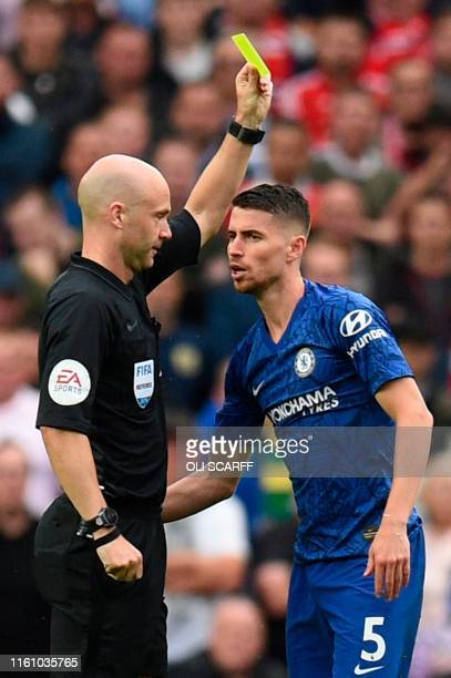 Chelsea's Italian midfielder Jorginho is shown a yellow card by referee Anthony Taylor during the English Premier League football match between...