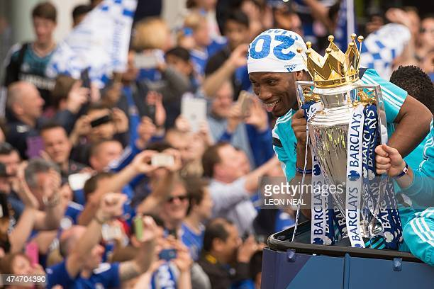Chelsea's Ivorian striker Didier Drogba holds up the Premier league trophy to fans as the Chelsea team take part in an opentop bus parade through...