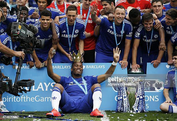 Chelsea's Ivorian striker Didier Drogba wears the crown holding a camera as he poses with his teammates including Chelsea's Serbian midfielder...