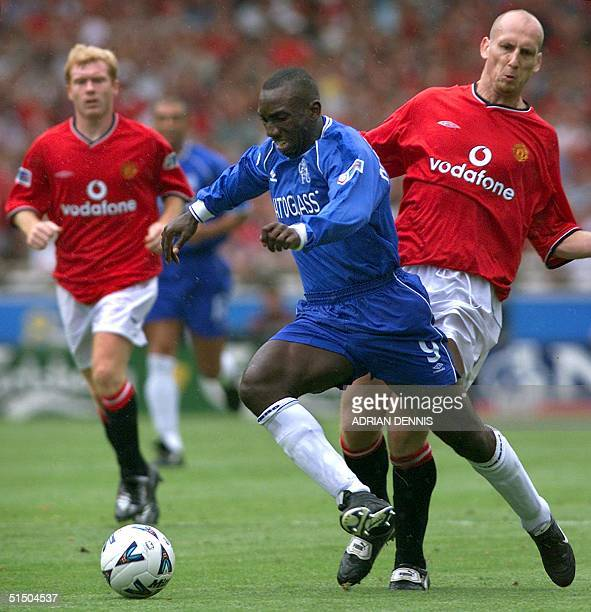 Chelsea's Jimmy Floyd Hasselbaink their new summer signing dribbles the ball past Manchester United's Jaap Stam while Paul Scholes looks on during...