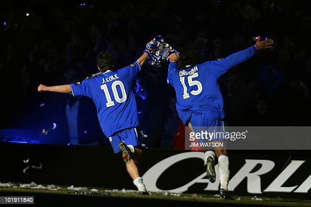 Chelsea's Joe Cole and Didier Drogba run with the Carling Cup trophy after defeating Liverpool in the Carling Cup Final football match at the...