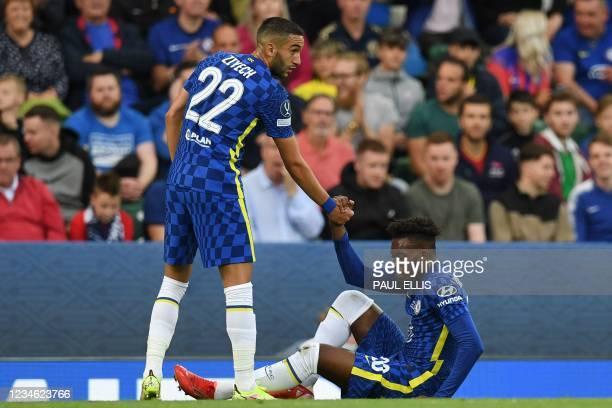 Chelsea's Moroccan midfielder Hakim Ziyech helps up Chelsea's English midfielder Callum Hudson-Odoi during the UEFA Super Cup football match between...