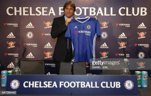 Chelsea's newly appointed Italian manager Antonio Conte holds a Chelsea football shirt as he poses for photographs during a press conference at the...