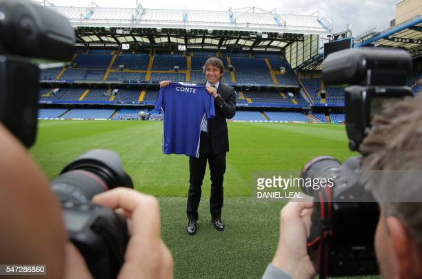 Chelsea's newly appointed Italian manager Antonio Conte holds a Chelsea football shirt as he poses for photographs on the pitch at the club's...