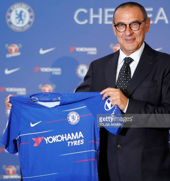 Chelsea's newly appointed manager, Maurizio Sarri, holds up a team football shirt as he attend his unveiling press conference at Stamford Bridge in...
